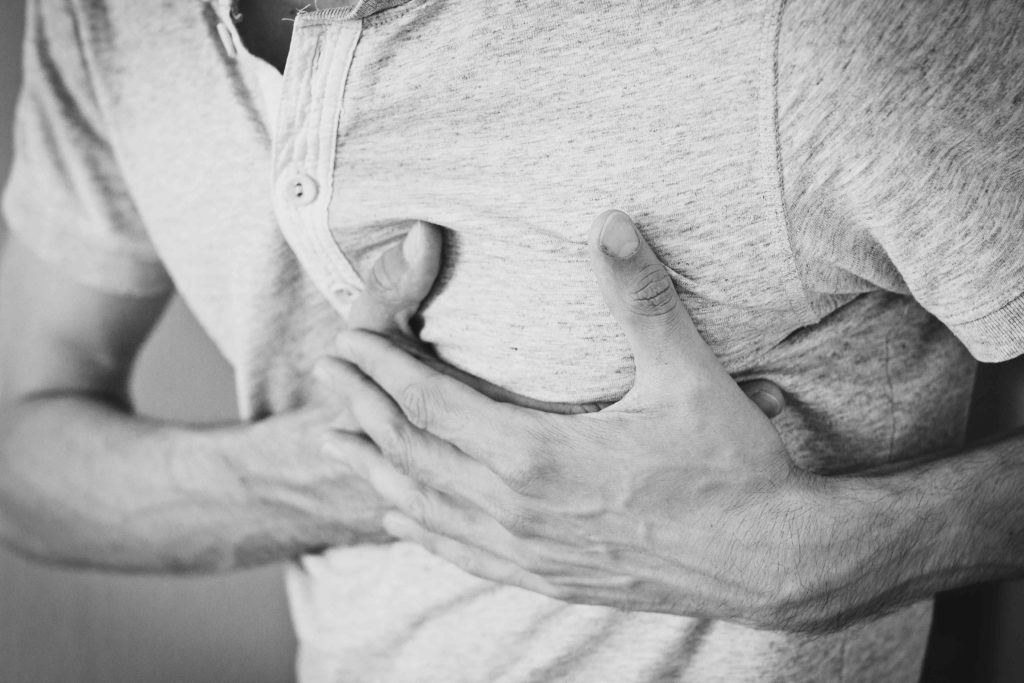 wounded healer man holding his chest heart attack