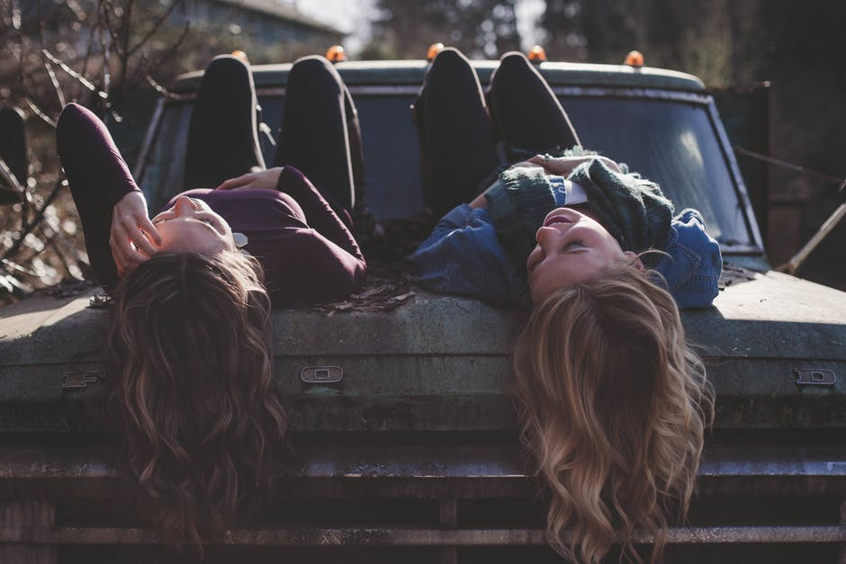 friendships weakness connections two girls laying down on hood of car