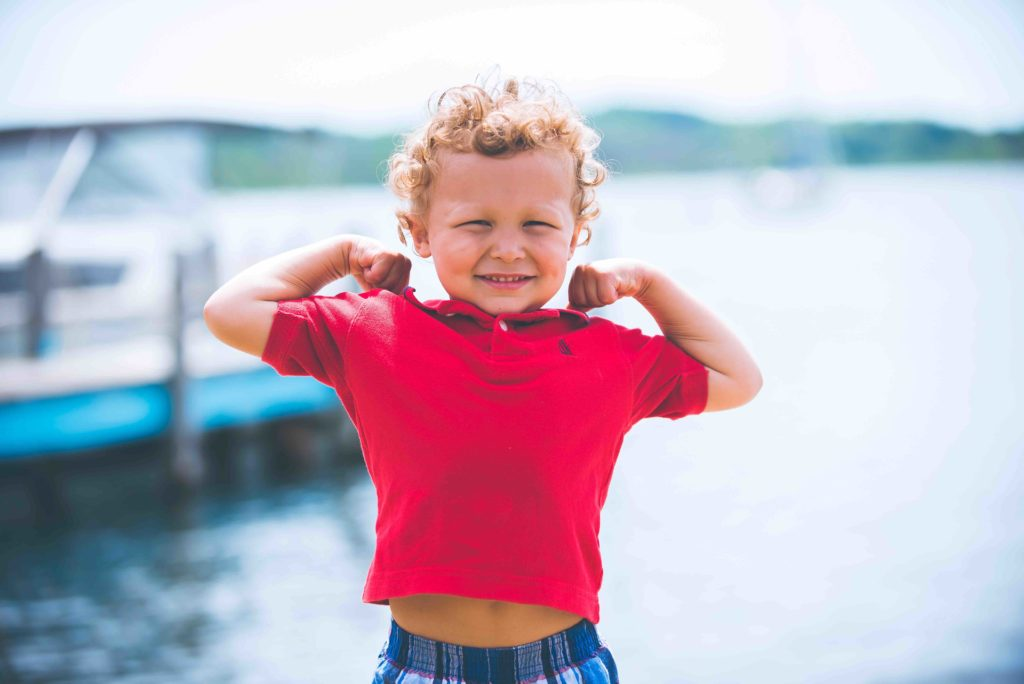 courage hope hero boy curly hair flexing arms